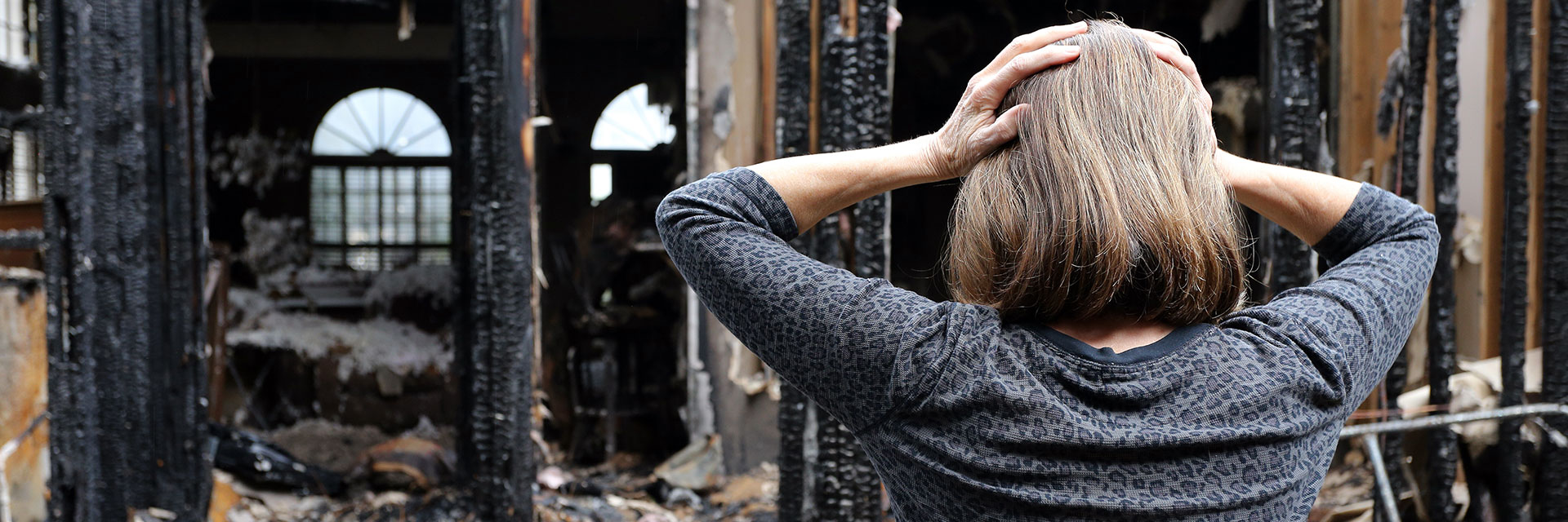 Woman distressed with hands on her head looking at her burnt down house