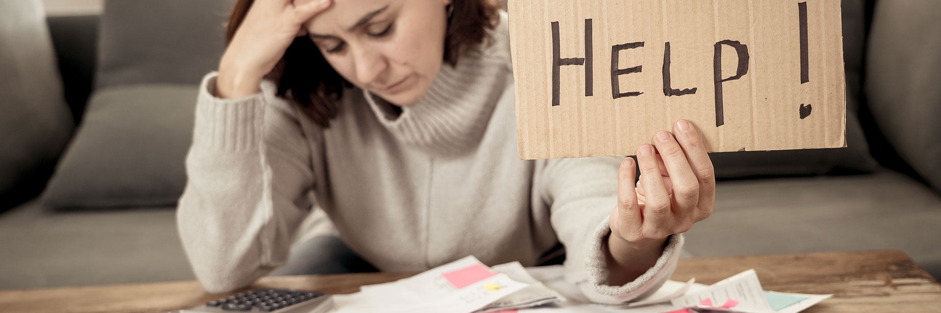 Woman stressed out filing an insurance claim holding up a sign saying Help