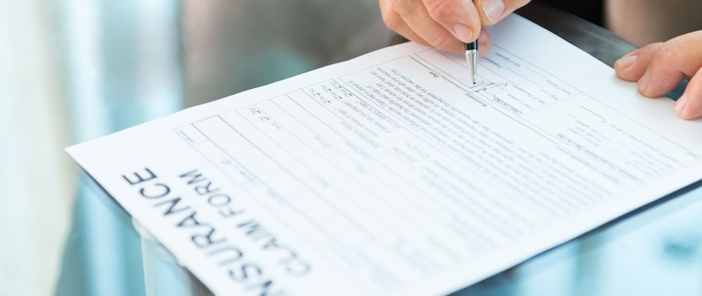 Closeup of a man's hand signing an insurance claim form