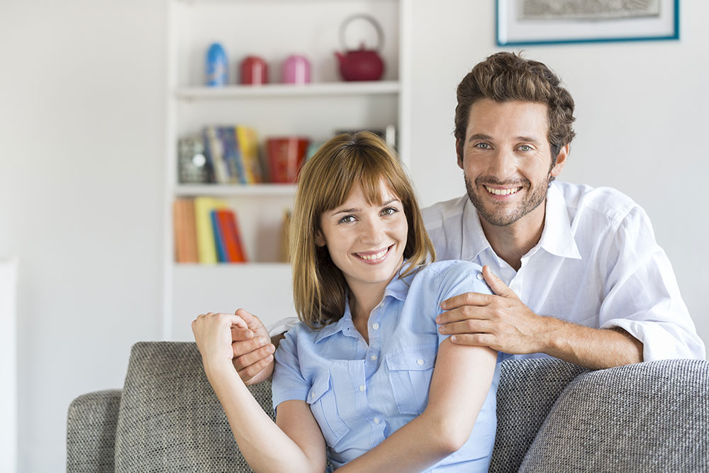 Portrait of cheerful thirty year old couple sitting on sofa in modern white apartment