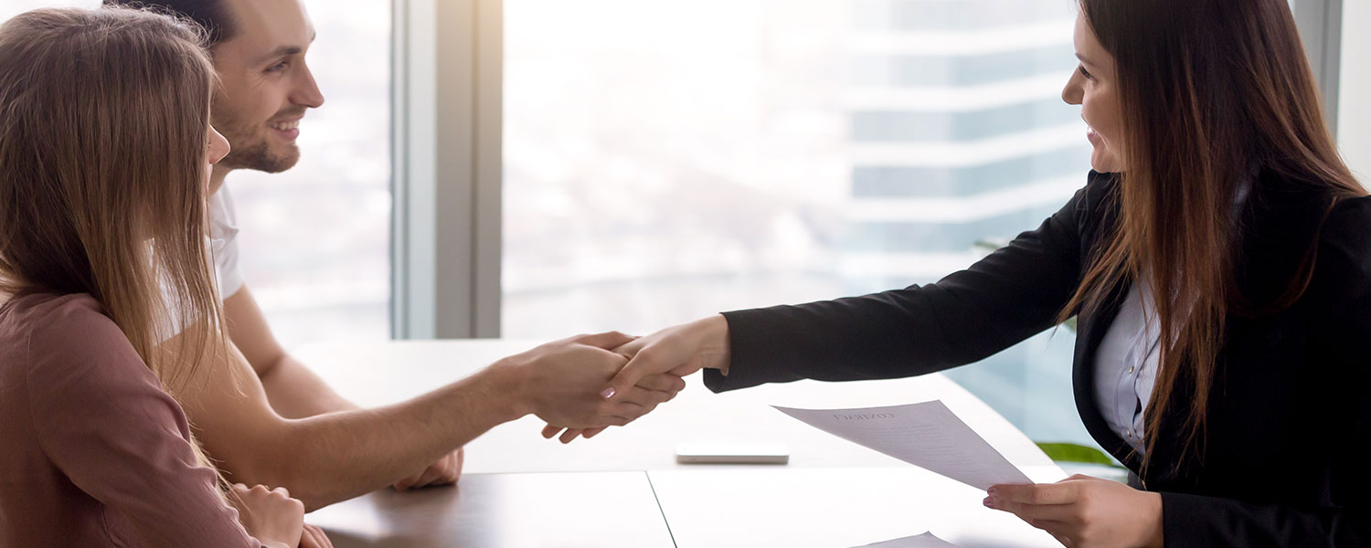 Young smiling couple visiting real estate agency shaking hands with realtor